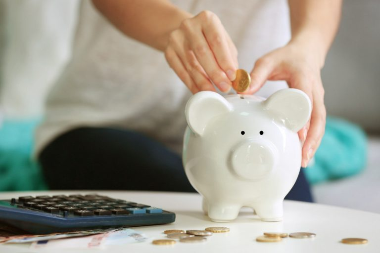 Woman placing a coin in a piggy bank