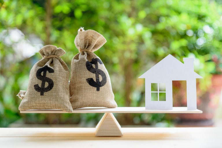 Moneybags and small home on miniature seesaw Volt Credit Union Mortgage Loan Amount
