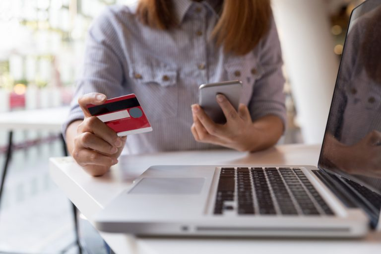 Young woman's hands holding a debit card and phone