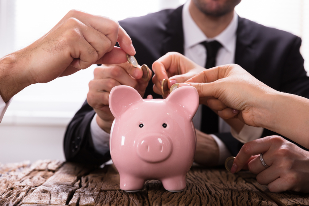 Credit union concept several hands putting coins in a piggy bank