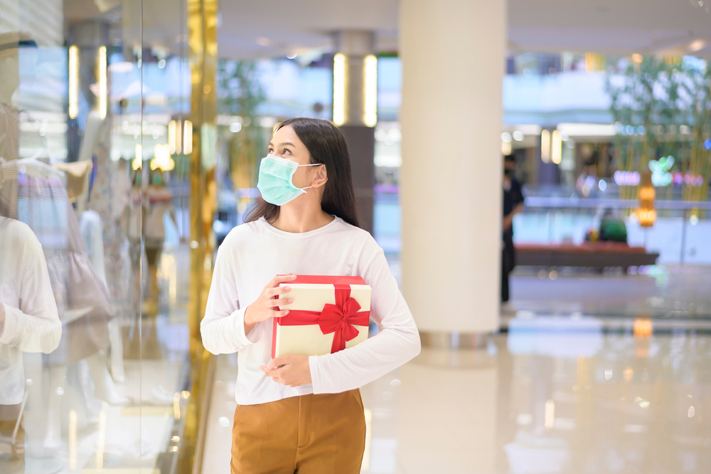 Woman wearing face mask holding a Christmas gift in a shopping mall