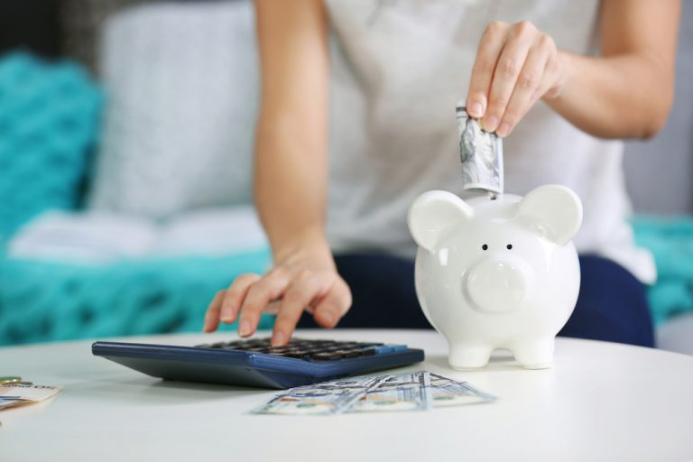 Female hand putting a $100 bill into a piggy bank and adding it on a calculator