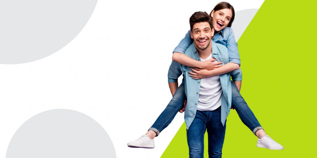 young guy and girl against a green and white background, girl is riding piggy back on guy and they are laughing