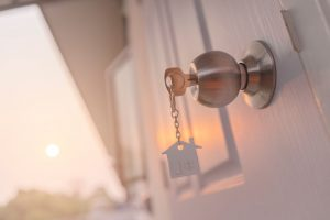 image of a house on a keychain in doorknob at sunset