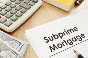 image of a subprime mortgage writing on paper on a wooden desk next to a calculator